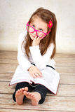 Bored little schoolgirl wearing glasses and reading book Stock Images