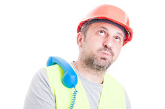 Bored male constructor waiting for a call. Bored male constructor with hardhat and protection vest waiting for a call isolated on white background Royalty Free Stock Photography