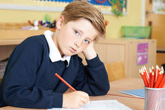 Bored Male Elementary School Pupil At Desk Stock Images