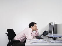 Bored Male Office Worker At Desk. Side view of a bored male office worker looking at notes on computer monitor at desk Royalty Free Stock Photography