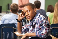 Bored Male Teenage Pupil In Classroom. Looking At Camera Leaning On Desk Stock Photo