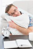 Bored man beside alarm clock Royalty Free Stock Images