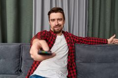 Bored man changing channels on TV. Bored bearded man grimacing and using remote control to change channels on TV set while sitting on couch and relaxing at home royalty free stock photography