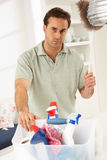 Bored Man Cleaning Light Fitting Stock Image