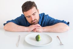 Sad and frustrated man on diet having only vegetables for meal Stock Photography