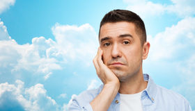 Bored man face over blue sky and clouds background Stock Photos
