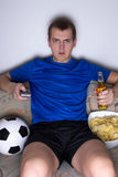 Bored man in football uniform sitting in living room and watchin Royalty Free Stock Photos