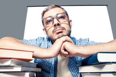 Bored man in glasses. Bored young man in glasses with books looking at camera Stock Photo