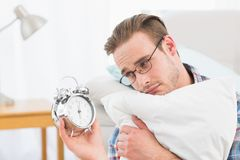 Bored man holding alarm clock Royalty Free Stock Images