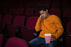 Man with popcorn sleeping in theatre. Bored man with popcorn sleeping in theatre Stock Photo