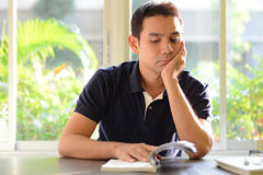 Bored man reading book with hand on chin Stock Photos