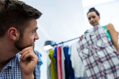 Bored man with shopping bags while woman by clothes rack. Bored men with shopping bags while women by clothes rack at clothes store Royalty Free Stock Photography
