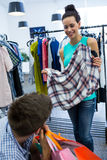Bored man with shopping bags while woman by clothes rack. Bored men with shopping bags while women by clothes rack at clothes store Royalty Free Stock Images