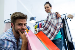 Bored man with shopping bags while woman by clothes rack. Bored men with shopping bags while women by clothes rack at clothes store Stock Photography