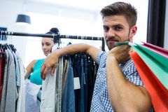 Bored man with shopping bags while woman by clothes rack. Bored men with shopping bags while women by clothes rack at clothes store Royalty Free Stock Photos