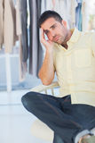 Bored man sitting in a clothing store Stock Photos