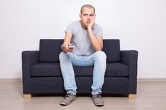 Bored man sitting on sofa and watching tv Stock Photos