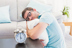 Bored man on the table beside alarm clock Stock Images