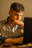 Bored man using laptop Stock Images