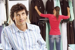 Bored man waiting in clothes shop, girlfriend choosing tops from rail in background, focus on foreground Stock Images