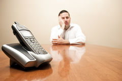 Bored man waits for the phone. Bored man in business shirt waits for a call Stock Images