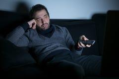 Bored man watching television at night Royalty Free Stock Images
