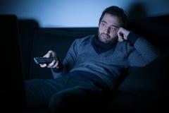 Bored man watching television at night Stock Photography