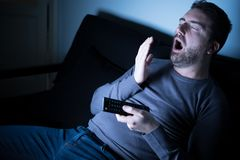 Portrait of man yawning and watching tv Royalty Free Stock Photography