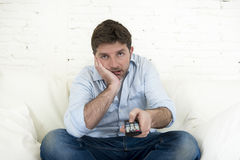 Bored man watching television sitting on sofa holding remote control tired not having fun Royalty Free Stock Image