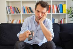 Free Bored Man Watching Tv In The Living Room Stock Photos - 121388613