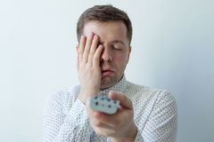 Bored man watching tv and zapping closing face with hand. Change TV programm Stock Image