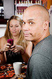 Bored man with woman on cell phone royalty free stock photo