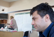 Bored man at workshop. Bored young man at workshop with lecturer in background Royalty Free Stock Photo