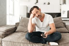 Bored mature man sitting on a sofa. With TV remote control at home Stock Images