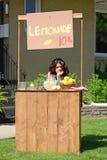 Bored meisje bij limonadetribune Royalty-vrije Stock Afbeeldingen