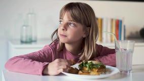 Bored meisje die zijdelings terwijl thuis het eten van een volledige hamburger met aardappels kijken stock videobeelden