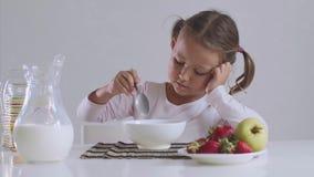 Bored meisje wil geen cornflakes met melk voor ontbijt eten stock videobeelden