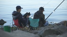 Bored men catching fish, using tablet to search tutorials on fishing websites