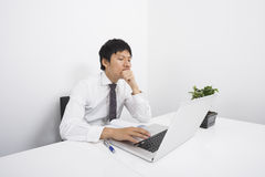 Bored mid adult businessman using laptop at desk in office Royalty Free Stock Photography