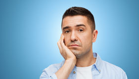 Bored middle aged man face over blue background Royalty Free Stock Images