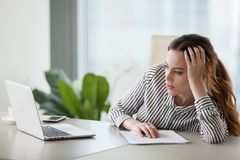 Bored woman worker feel unmotivated at work. Bored millennial female worker lie at office desk look at laptop screen think about problem solution, unmotivated stock photography