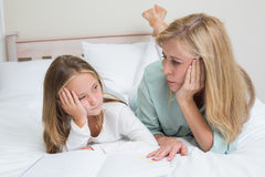 Bored mother and daughter reading a book Royalty Free Stock Photography