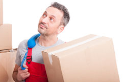 Bored mover guy holding box and telephone receiver Stock Image