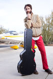 Bored musician at the airport with guitar Stock Photo
