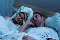 Bored paar die in bed liggen royalty-vrije stock afbeelding