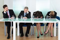 Bored panel of judges or interviewers. Bored panel of professional judges or corporate interviewers lounging around on a table napping as they wait for something Royalty Free Stock Photo