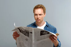 Bored person looking into newspaper Royalty Free Stock Images