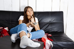 Bored pretty girl watching tv, sitting on sofa at home. Royalty Free Stock Images
