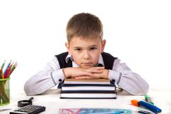 Bored pupil sitting at the desk with head on the pile of books surrounded with stationery stock image