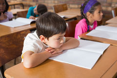 Bored pupil sitting at his desk Royalty Free Stock Photography
